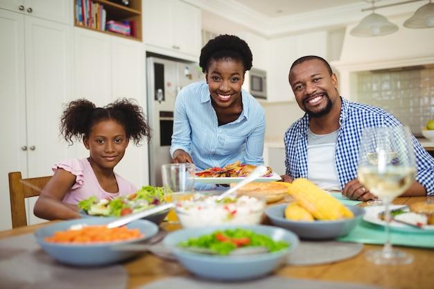 Retrato de mulher feliz servindo comida para a família