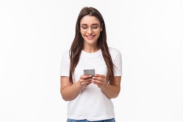 Retrato de mulher feliz sorridente carismática usando telefone celular, segurando smartphone, conversando com amigos enquanto está sentado em casa, rolar o feed da internet