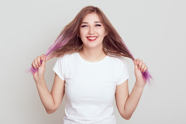 Retrato de mulher feliz sorridente de jovem olhando para a câmera com um sorriso dentuço, puxando o cabelo de lado, tem olhar engraçado, vestindo camiseta branca casual, isolado sobre fundo cinza.