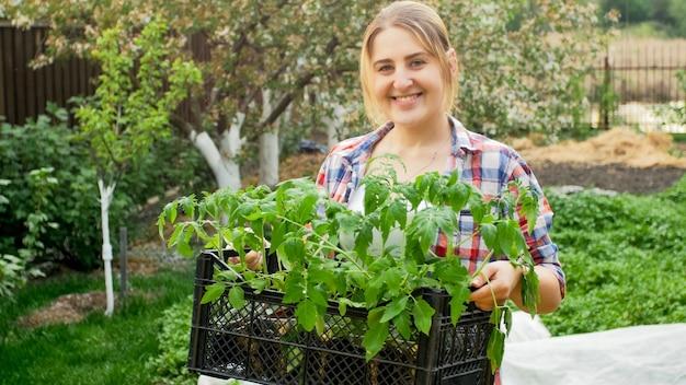 Retrato de mulher feliz sorridente segurando caixa com mudas posando no jardim.