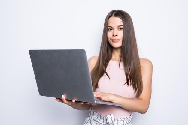 Retrato de mulher feliz surpresa em pé com laptop isolado na parede cinza.