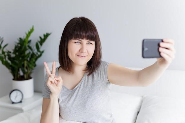 Retrato de mulher feliz tirando foto de selfie com telefone inteligente em casa