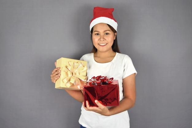 Retrato de mulher feliz usando chapéu de papai noel e segurando a caixa de presente.