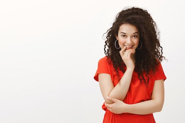 Retrato de mulher feminina atraente e atraente com cabelo encaracolado, sorrindo intrigantemente e segurando ching