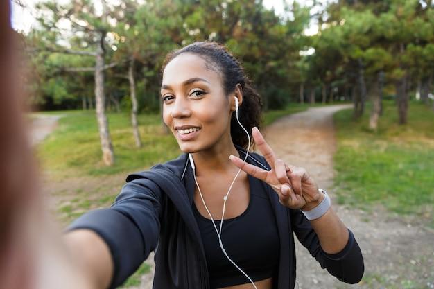 Retrato de mulher feminina de 20 anos, vestindo um agasalho esportivo preto e fones de ouvido, tirando uma foto de selfie no celular enquanto caminha pelo parque verde