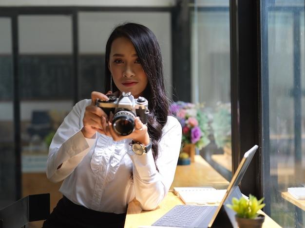 Retrato de mulher fotográfica verificando foto na câmera digital enquanto trabalhava em estúdio
