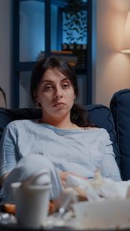 Retrato de mulher frustrada e traumatizada sentada sozinha no sofá