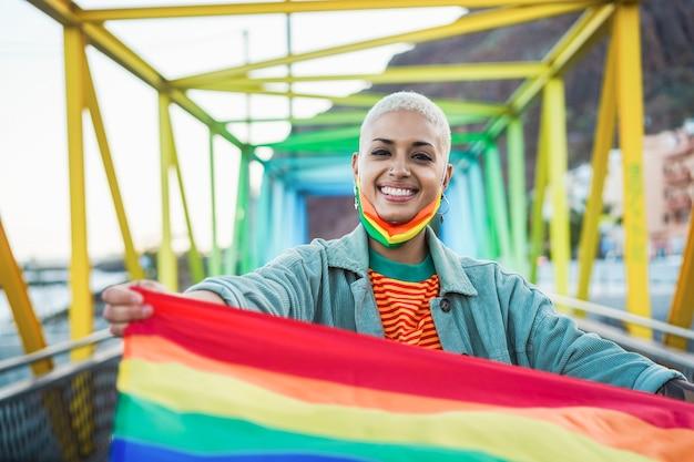 Retrato de mulher gay com máscara facial segurando uma bandeira do arco-íris - conceito de direitos lgbt - foco no rosto da menina