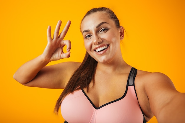 Retrato de mulher gordinha alegre em sutiã esportivo usando telefone celular para foto de selfie, isolado sobre fundo amarelo