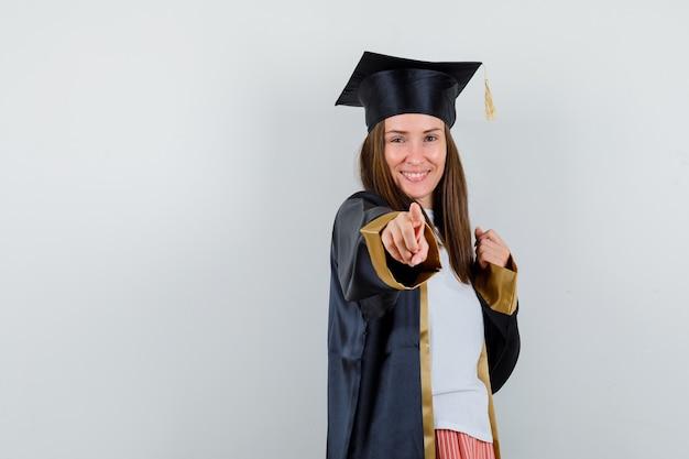 Retrato de mulher graduada apontando para a câmera em uniforme, roupas casuais e olhando alegre de frente