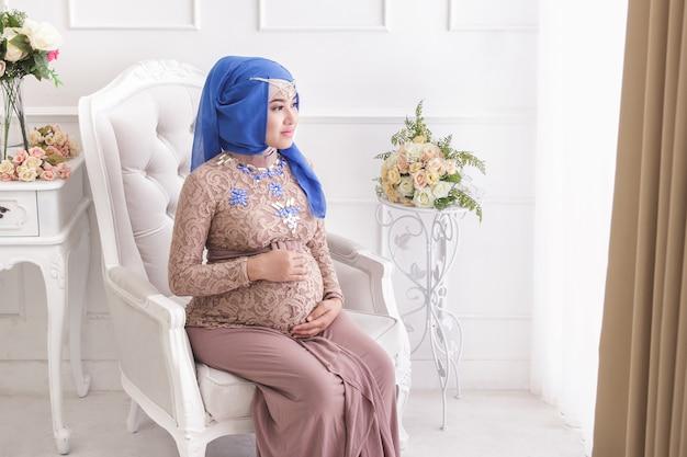 Retrato de mulher grávida asiática usando hijab, sentada no sofá