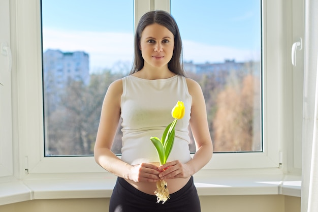 Retrato de mulher grávida com uma flor de tulipa amarela