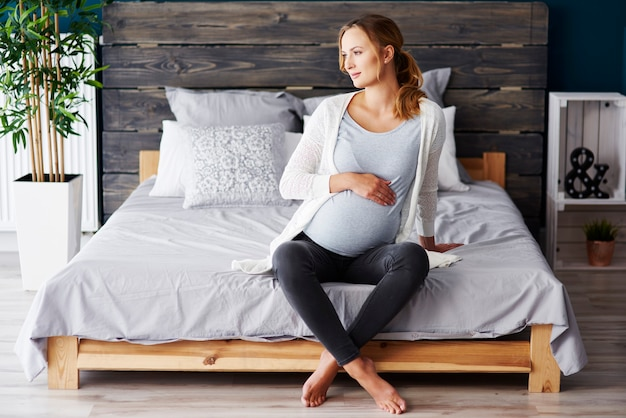 Retrato de mulher grávida descansando no quarto