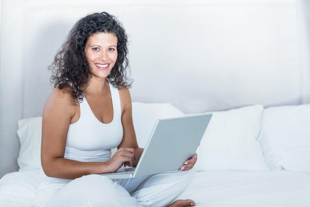 Retrato de mulher grávida linda usando laptop