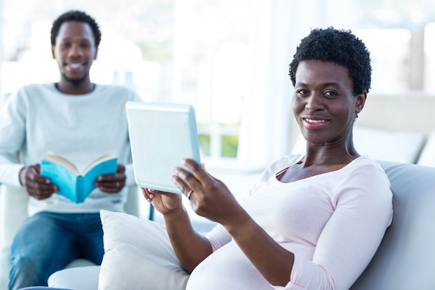 Retrato de mulher grávida segurando comprimido digital enquanto está sentado no sofá