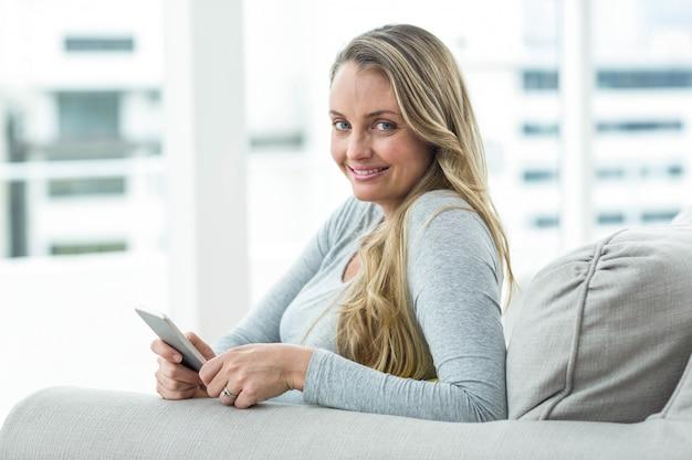 Retrato, de, mulher grávida, sentar sofá, e, usando, smartphone