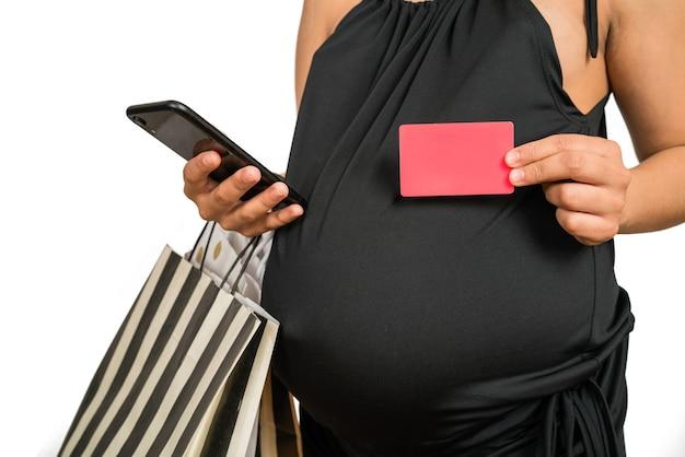 Retrato de mulher grávida usando cartão de crédito e celular para compras online contra fundo branco. conceito de loja online.