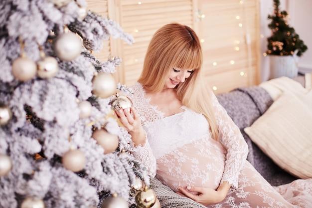 Retrato de mulher grávida, vibrações de ano novo. encantadora loira esperando mulher se senta