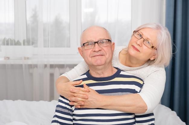 Retrato de mulher idosa abraçando um homem sênior em casa