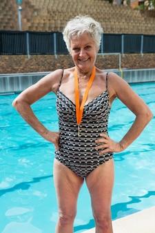 Retrato de mulher idosa animada com medalhas de ouro no pescoço, em pé à beira da piscina
