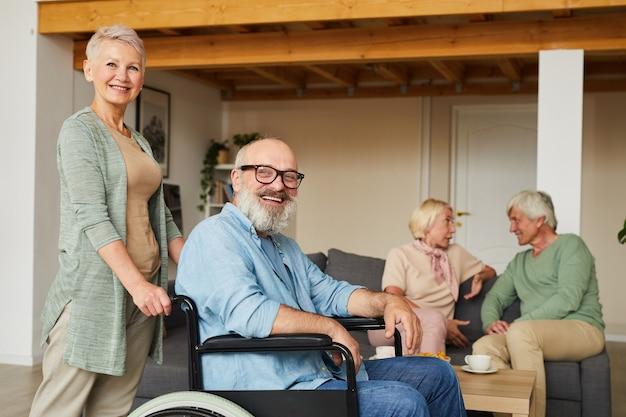 Retrato de mulher idosa com homem deficiente em cadeira de rodas, sorrindo para a câmera com outras pessoas