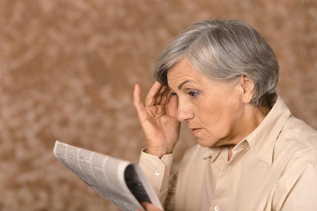 Retrato de mulher idosa e felizmente surpresa lendo jornal