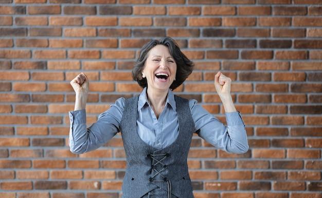 Retrato de mulher idosa feliz linda recrutada em traje de negócios. excelente conceito de boas notícias