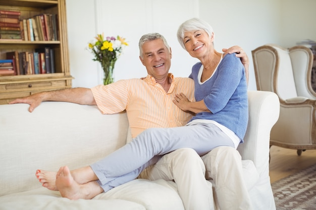 Retrato de mulher idosa sentada no colo do homem na sala de estar