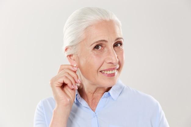 Retrato de mulher idosa sorridente, tocando sua orelha