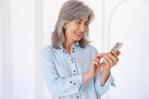Retrato de mulher idosa usando dispositivo smartphone