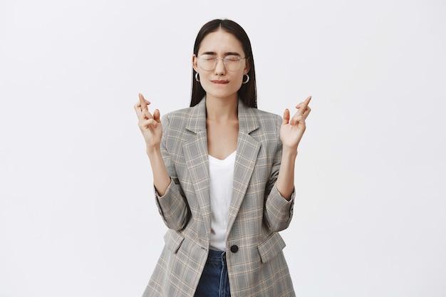 Retrato de mulher intensa e atraente de óculos e jaqueta, fechando os olhos e franzindo os lábios enquanto cruza os dedos