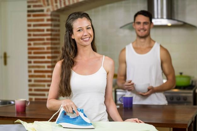 Retrato, de, mulher, ironing, um, camisa, enquanto, homem, tendo, café manhã, em, fundo
