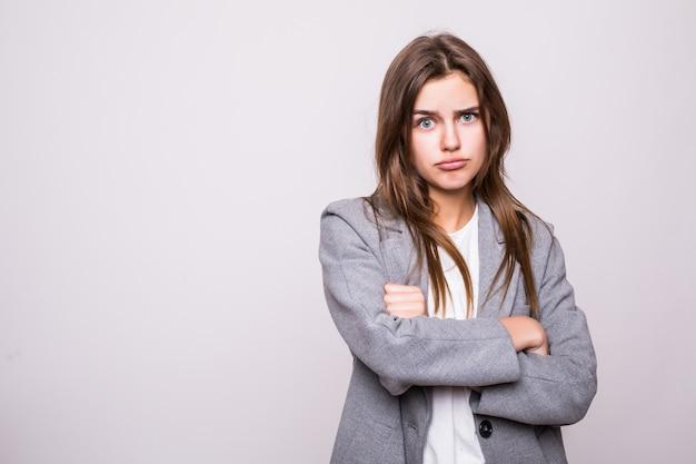 Retrato de mulher irritada em pé com os braços cruzados, isolado no fundo cinza