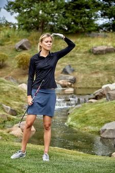 Retrato de mulher jogando golfe em um campo verde