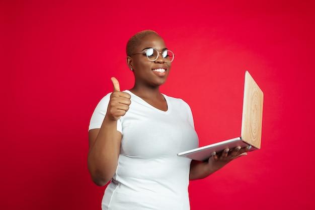 Retrato de mulher jovem afro-americana em fundo vermelho