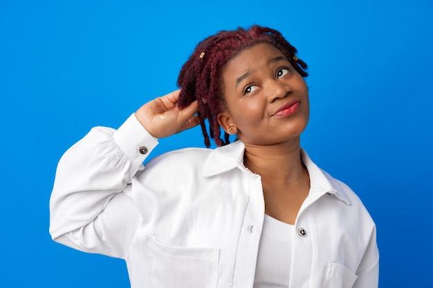 Retrato de mulher jovem afro-americana pensativo contra um fundo azul.