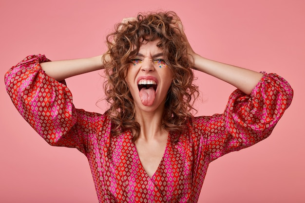 Retrato de mulher jovem animada, gritando alto e mostrando a língua, cobrindo os ouvidos com as mãos, em pé. vestindo roupas listradas rosa e laranja