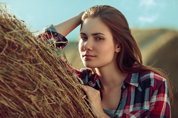 Retrato de mulher jovem ao lado de uma pilha de feno sob a luz do sol