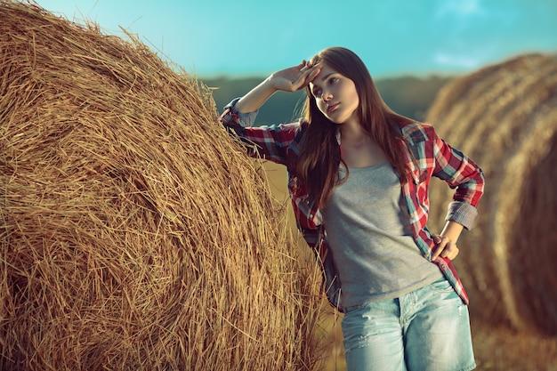Retrato de mulher jovem ao lado de uma pilha de feno