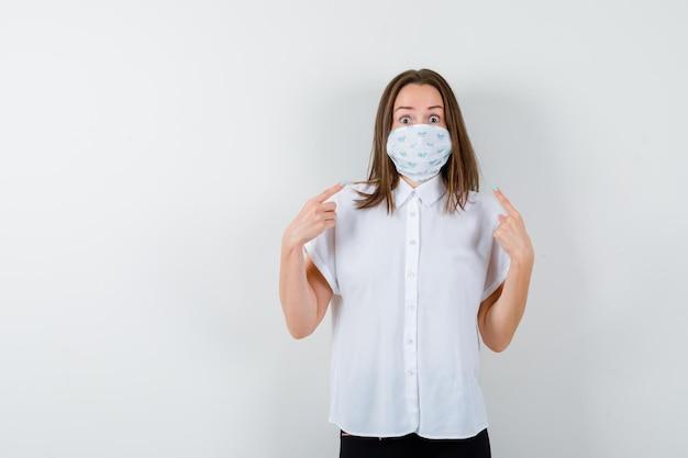 Retrato de mulher jovem apontando para sua máscara médica