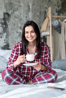 Retrato de mulher jovem, aproveitando a manhã na cama