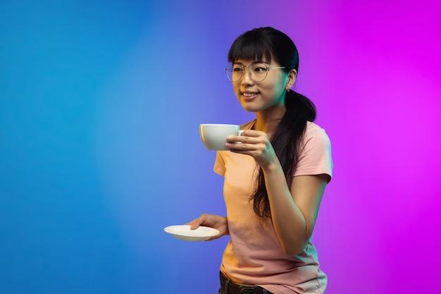 Retrato de mulher jovem asiática em fundo gradiente de estúdio em néon