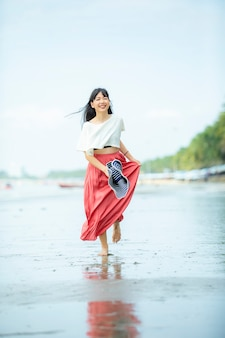 Retrato de mulher jovem asiática feliz na praia de férias