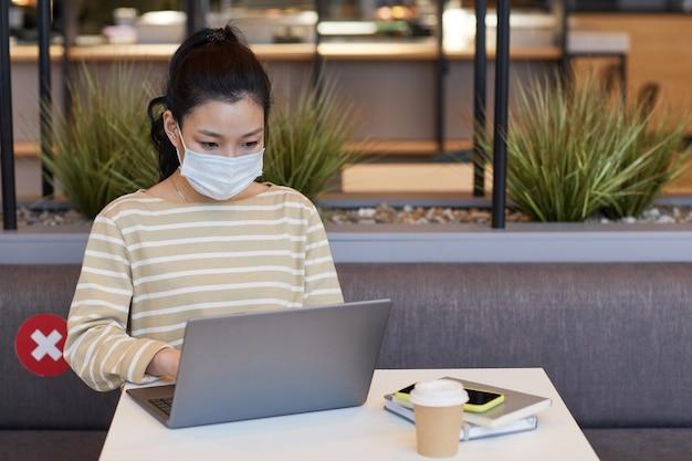 Retrato de mulher jovem asiática usando máscara enquanto trabalhava na mesa de um café com adesivo de distanciamento social, segurança cobiçosa, espaço de cópia