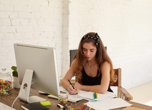 Retrato de mulher jovem atenta, estudando línguas estrangeiras no site da internet, fazendo anotações em adesivos para memorizar melhor as novas palavras. copie a parede do espaço para conteúdo ou texto publicitário.