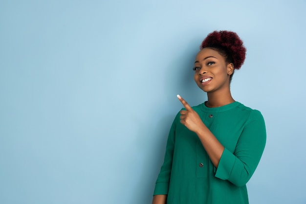 Retrato de mulher jovem bonita afro-americana sobre fundo azul do estúdio, expressivo emocional.