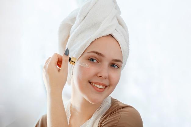 Retrato de mulher jovem bonita aplica óleo de soro em produto cosmético de conta-gotas para pele de cuidados com a pele do rosto saúde no reflexo do espelho com toalha na cabeça. o autocuidado como parte da rotina matinal do banheiro.