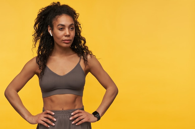Retrato de mulher jovem bonita e confiante em pé, usando fones de ouvido sem fio e relógio inteligente isolado sobre a parede amarela