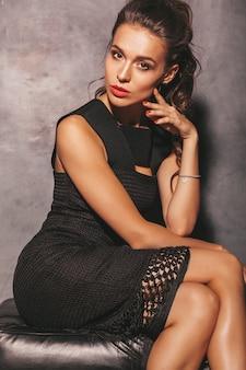 Retrato de mulher jovem bonita hipster em vestido preto verão na moda. mulher despreocupada sexy posando perto da parede. modelo moreno com maquiagem e penteado. sentado na cadeira