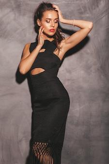 Retrato de mulher jovem bonita hipster em vestido preto verão na moda. mulher despreocupada sexy posando perto da parede. modelo moreno com maquiagem e penteado